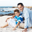 Royalty-Free Stock Photo: Loving father and son sitting at the sandy beach