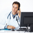 Thoughtful doctor using telephone while sitting his office desk - Stock Photo