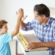 Mission accomplished - Father and son giving high five after mak - Stock Photo