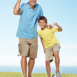 Royalty-Free Stock Photo: Excited father and son standing outside with a football