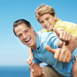 Royalty-Free Stock Photo: Man giving his son piggy back ride and showing thumbs up