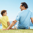 Royalty-Free Stock Photo: Happy man and his son sitting relax on grass