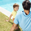 Royalty-Free Stock Photo: Mature man and his little son sitting at swimming pool