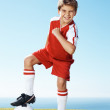 Exited little boy with soccer ball standing outside - Stock Photo