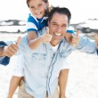 Royalty-Free Stock Photo: Happy father and son on the beach with thumbs up