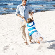 Royalty-Free Stock Photo: Happy man swinging his son at the beach