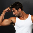 Handsome muscular man flexing his biceps - Stockfoto