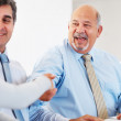 Happy business leaders handshaking at meeting - Foto Stock