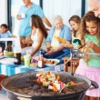 Girl and grandfather at the barbecue grill with family in backgr - Stock Photo