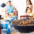 Focus on barbecue with family in background - Stock Photo