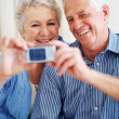 Happy senior couple taking a self portrait on mobile phone - Stockfoto