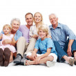 Happy family sitting together on floor - Stock Photo