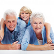 Happy old couple lying on floor with a their grandson - Stock Photo