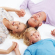Royalty-Free Stock Photo: Happy family lying on floor in a circle and holding hands