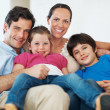 Royalty-Free Stock Photo: Happy parents with kids on couch