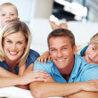 Couple with kids relaxing at home - Stock Photo