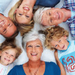 Multi generation family lying down together - Stock Photo