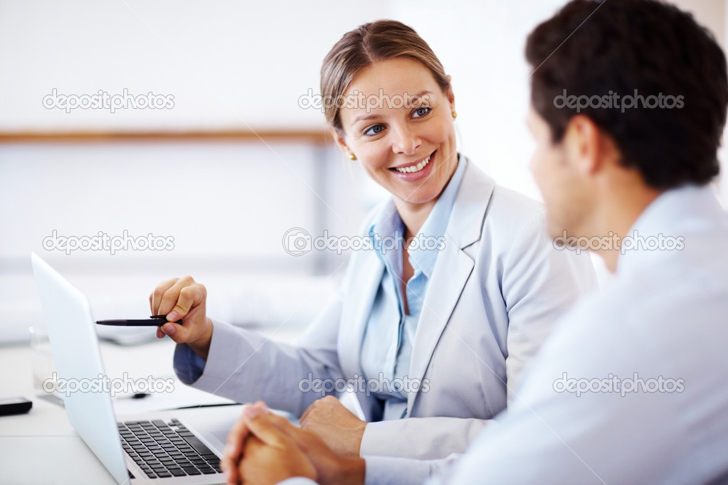 Happy young businesswoman points something out to her colleague on a laptop at office — Foto Stock #7840717