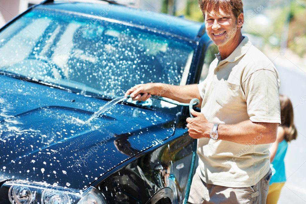 Portrait of man washing his car and smiling with daughter in background — Stock Photo #7841509