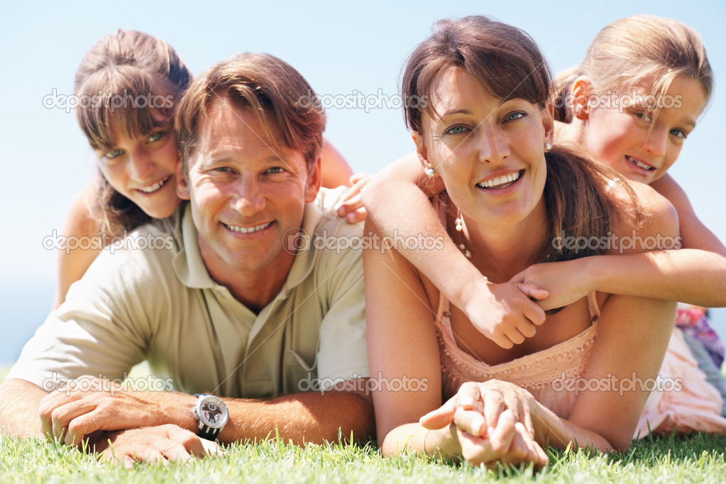 Portrait of family lying together on grass and smiling — Stock Photo #7841583