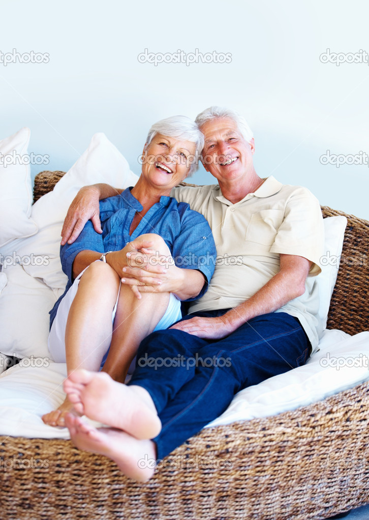 Portrait of senior couple sitting together on a sofa and smiling — Stock Photo #7841760