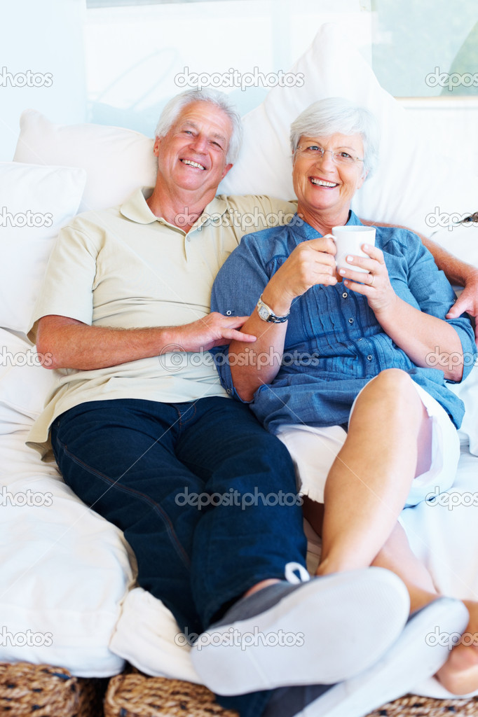 Portrait of senior couple sitting together on a sofa with woman holding a cup of coffee — Stock Photo #7841877