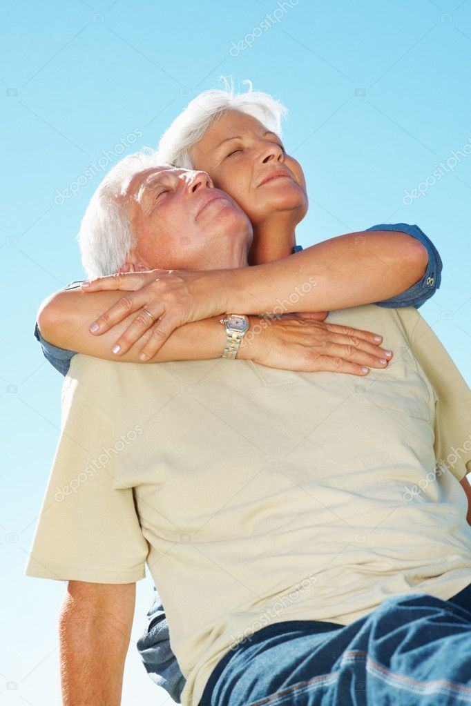 Senior couple enjoying the tranquil weather with woman embracing man from behind — Stock Photo #7842076