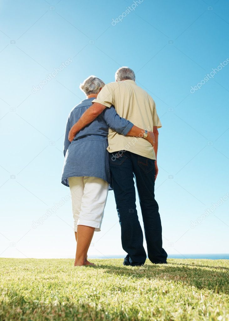 Rear view of senior couple standing together on grass with arms around  Stock Photo #7842094