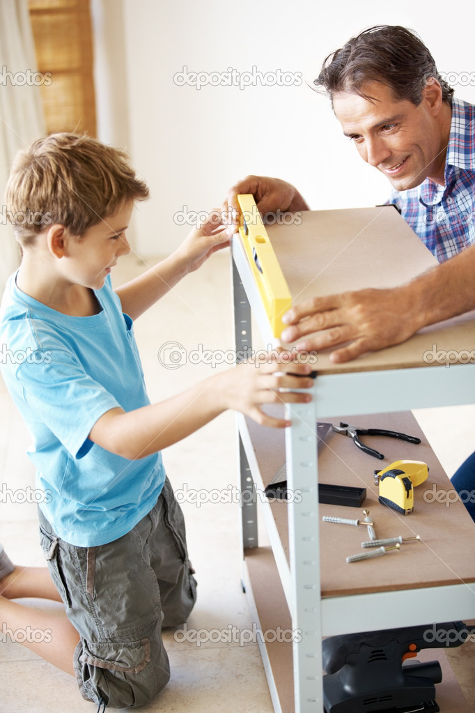 Portrait of mature father teaching his little son how to check leve with spiritlevel in workshop — Stock Photo #7842509