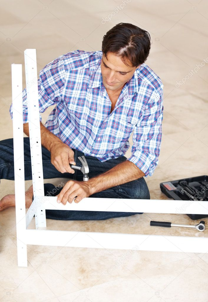 Manual worker working on a metal rack with a hammer in his workshop  Photo #7842931