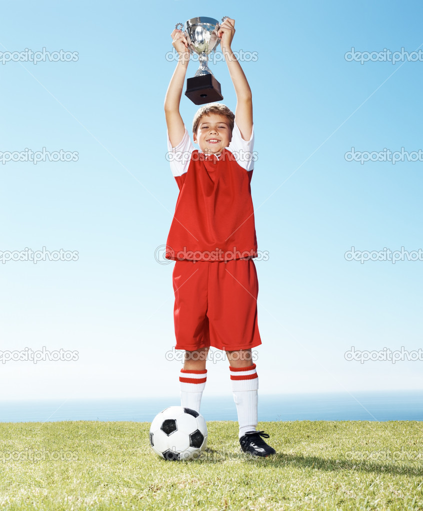 Portrait of a happy little boy holding up a winners trophy with football at ground — Stock Photo #7843043