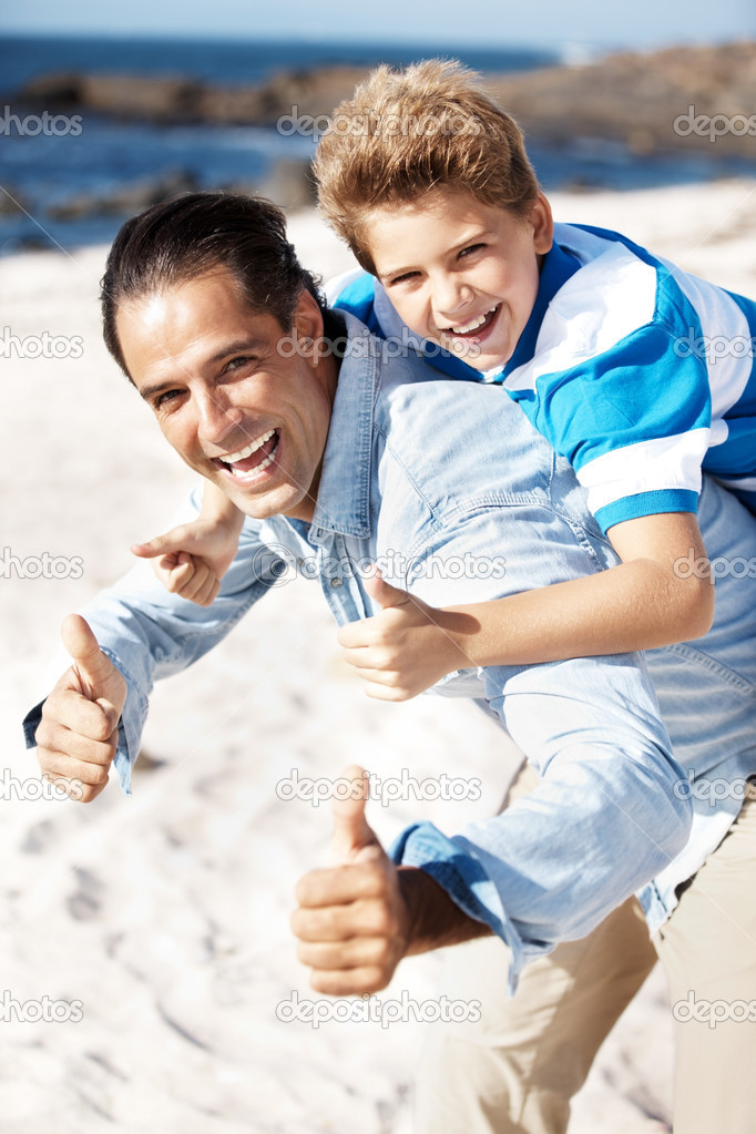 Portrait of a happy father giving his son piggyback ride and gesturing thums up sign at the beach — Foto Stock #7843070