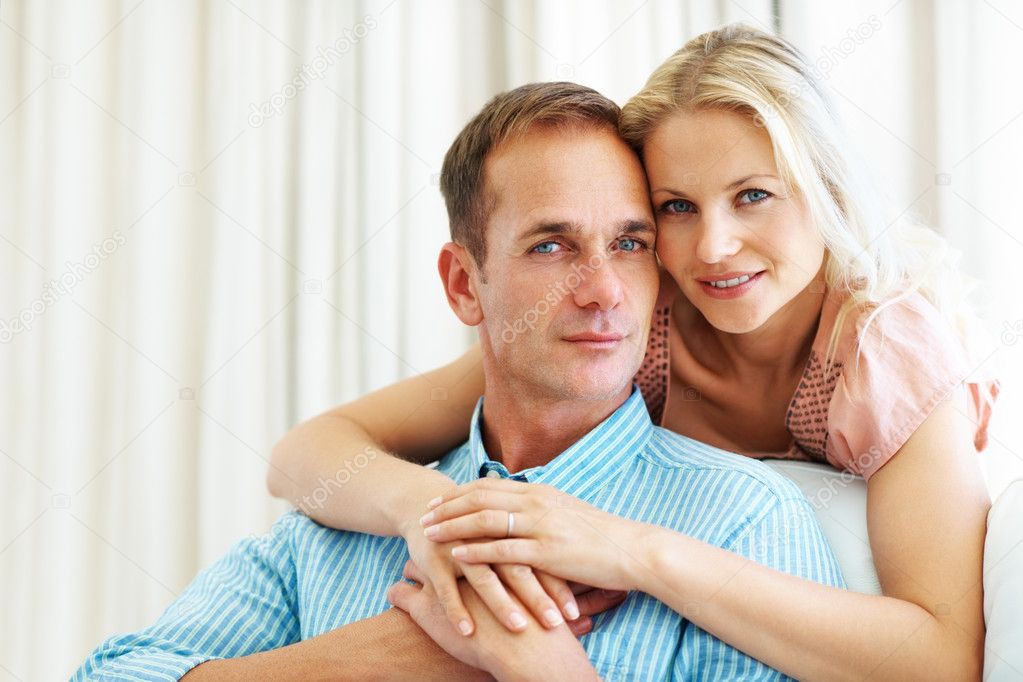 Portrait of a cute woman hugging her husband from behind at home — Stock Photo #7845026