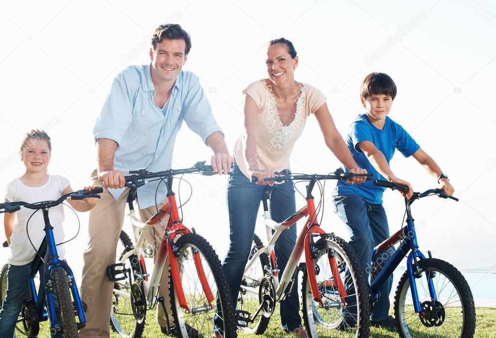 Happy middle aged couple with children riding bikes in park — Photo #7848325