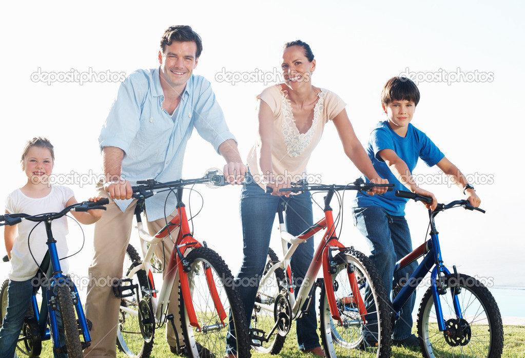 Happy middle aged couple with children riding bikes in park — Zdjęcie stockowe #7848325