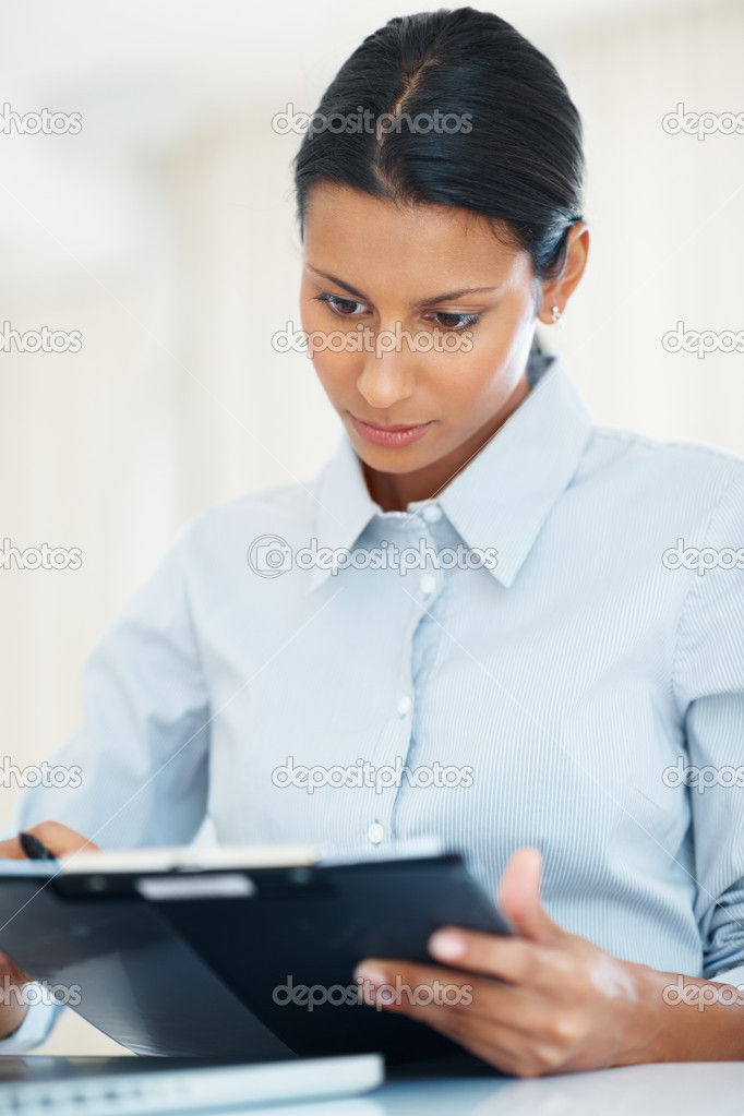 Modern female professional reviewing documents at workplace — Stock Photo #7849149