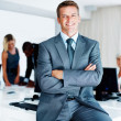 Smiling business man with colleagues in background - Stock Photo