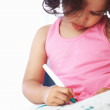 Girl coloring in color book - Stock Photo