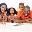 Family of four reading book together - Stock Photo