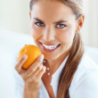 Smiling woman with orange - Stock Photo