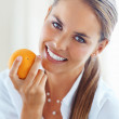 Healthy woman smiling with orange - Stock Photo