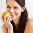 Pretty woman smiling with orange - Stock Photo