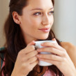 Young woman having coffee - Stock Photo