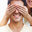 Woman covering man's eyes - Stock Photo