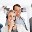 Royalty-Free Stock Photo: Business woman in headphones smiling with office colleagues