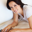 Royalty-Free Stock Photo: Happy woman using laptop on couch