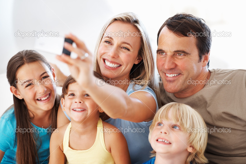 Portrait of happy family with children taking self portrait — Stock Photo #7850277