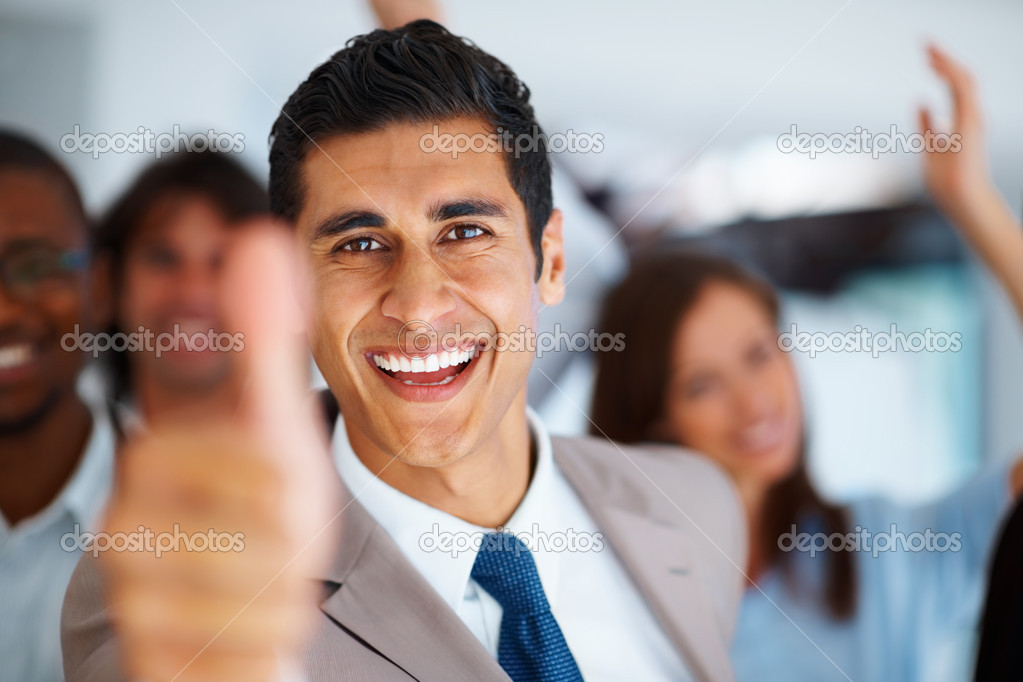 Successful business man giving you thumbs up with colleagues in background  Stock Photo #7850643