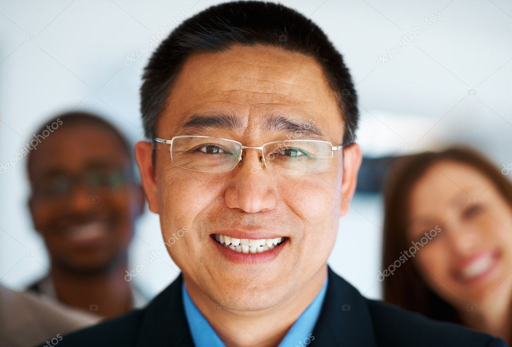 Closeup portrait of handsome mature business man standing in front of multi ethnic team — Stock Photo #7850657