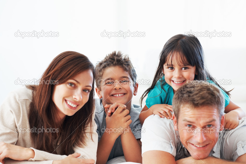 Portrait beautiful couple with cute kids smiling together while lying on floor — Stock Photo #7850979